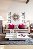 Sunburst mirror and black and white photographs above grey couch; crystal and glass ornaments on coffee table