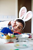 Boy wearing bunny ears painting Easter eggs