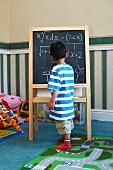 Boy standing beside blackboard with algebra