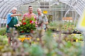 Senior gardener serving mature man and mid adult woman in garden centre