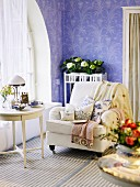 Gemütlicher Polsterstuhl und Beistelltisch im traditionellen skandinavischen Stil vor lila Tapete