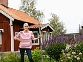 Smiling woman standing in front of house