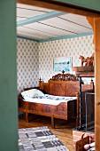 Blick durch offene Tür auf antikes Bett mit Seitenwand in ländlicher Schlafzimmerecke