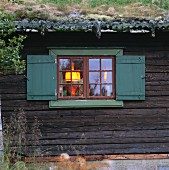 View of illuminated window of wooden house with green roof