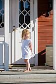 Little girl in white summer dress standing in front of front door