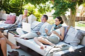 Casual business people on patio using laptop