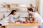 Junges, verliebtes Paar beim Frühstück in heller, freundlicher Küche