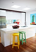 Coloured wooden bar stools in front of white kitchen island with sink in open-plan designer kitchen