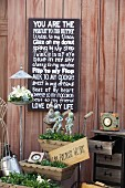 Wedding mottoes written on slate chalkboard above vintage, planted troughs