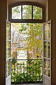 View through open windows out to garden with topiary and fountains