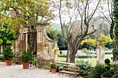 Iron gates leading to garden lawn with topiary and plane trees