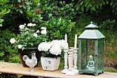 Garten-Stillleben mit weissen Blumen im Topf und Kerzenständer neben Laterne auf schlichter Holzbank