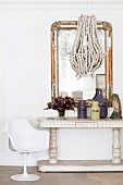 White tulip chair next to antique console table and hand-crafted pendant lamp in front of flyblown mirror