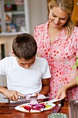 Mother helping a boy cutting an onion