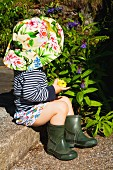 Toddler wearing sun hat and wellingtons sitting on stone step in garden