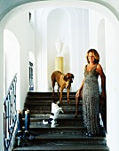 Woman in evening dress and dogs on staircase in front of arched niche in grand stairwell
