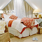 Romantic ambiance - various bedspreads on bed flanked by bedside lamps on tables in front of closed curtains on gable window