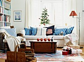 Pomegranates on wooden trunk in front of white sofa with blue and white striped scatter cushions below window in living room decorated for Christmas