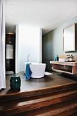 Freistehende Badewanne vor gebogener Wand in offenem Designerbad mit breiten Holzstufen