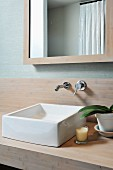 White washbasin on wooden surface below wall-mounted taps and framed mirror