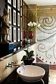 White washbasin on black stone surface and Oriental figurine on shelf next to shower area
