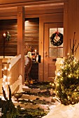 Front door and porch festively decorated with fir branches, door wreath & Christmas tree