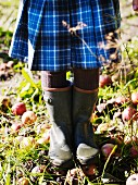 Girl wearing kilt & wellingtons standing amongst windfall apples