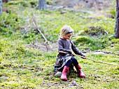 Mädchen sitzt auf Baumstumpf einer Waldlichtung und spielt mit einem Stock