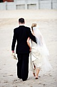 Bridal pair walking on sand