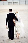 Bridal pair walking on sand
