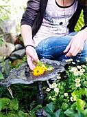 Teenage girl by a birdbath in a garden, Sweden.