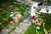 Woman planting in pots, Sweden.