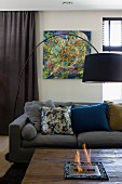 Arc lamp with black lampshade above coffee table with built-in bioethanol fireplace in front of sofa with various scatter cushions