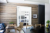 Black worksurface in front of dining area against rustic wooden wall and open double doors with view into living room