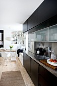 Modern kitchen counter with stainless steel worksurface and black-painted doors; vintage dining area with classic chairs in background