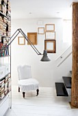 Books and storage boxes on steel shelving and chair with loose cover on white wooden floor; arrangement of picture frames and floating staircase in background