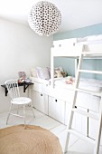 White, children's bedroom with black shelf and spherical paper lampshade with black polka dots; storage boxes integrated into bunk beds and country-house chair