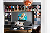Coffee table and grey sofa in front of modern bookcase and picture on grey wall; Poulsen pedant lamp in foreground