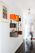 Colourful, cubic shelving units on wall in hallway; man in background