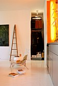 Modern living area with cloakroom niche and orange light installation above grey sideboard