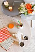 Weiss lasierter Kaffeetisch und Beistelltische aus Metall mit Blumendeko und Windlichtern in Grün und Orange