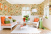 Lounge area with floral wallpaper above dado rail, white wall panelling below and orange and green accessories combined with white furniture