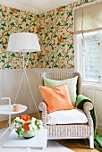 Wicker chair, standard lamp and side table against pale, wood-panelled dado and floral wallpaper above dado rail; orange and green accessories and flowers