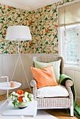 Helle Zone mit Korbstuhl, Stehlampe und Beistelltischen vor brüstungshoher Wandvertäfelung, getoppt von floral gemusterter Tapete; Accessoires und Blumen in Orange und Grün