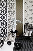 Black disco balls, side table, wicker chair and scatter cushion with print portrait in front of lengths of patterned wallpaper