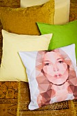Scatter cushions in yellow, green and gold and one with print portrait (Kate Moss)