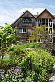 Overgrown, flowering garden in front of traditional wooden house with three-storey bay in Bergisches Land, Germany