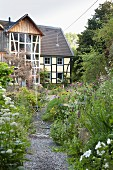 Flowering garden with sprinkler and half-timbered house