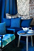 Seating area in blue with teapot, cup and notebook onside table