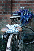 Bread wrapped in blue and white cloth on bicycle luggage rack with bouquet of lupins in crate on handlebars in front of brick wall